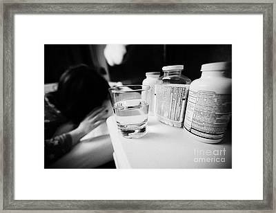 Glass Of Water And Bottles Of Pills On Bedside Table Of Early Twenties Woman Waking In Bed In A Bedr Framed Print by Joe Fox