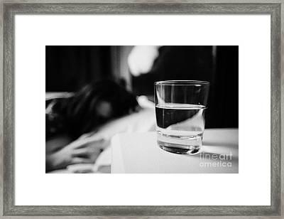 Glass Of Water On Bedside Table Of Early Twenties Woman In Bed In A Bedroom Framed Print by Joe Fox