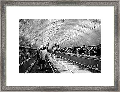 going down steep down escalator in tube station London England UK Framed Print