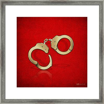 Gold Handcuffs On Red Leather Background Framed Print by Serge Averbukh