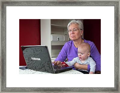 Grandmother And Baby Using A Computer Framed Print by Jim West