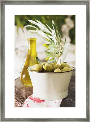 Green Olives, Olive Sprig And Olive Oil On Table Out Of Doors Framed Print