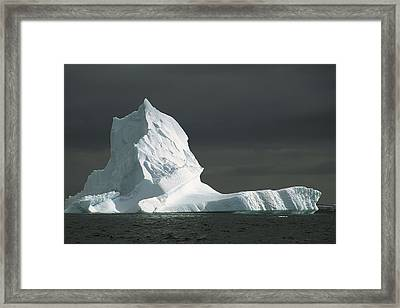 Grounded Iceberg With Storm Clouds Framed Print by Colin Monteath