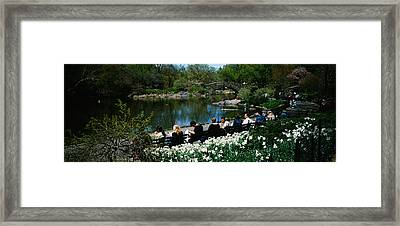 Group Of People Sitting On Benches Framed Print by Panoramic Images