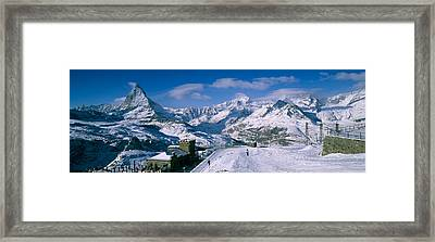 Group Of People Skiing Near A Mountain Framed Print by Panoramic Images