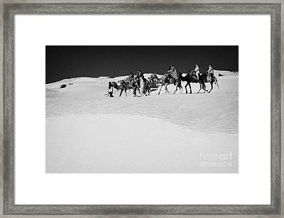group of tourists in desert dress on camel back being taken through the sand dunes and ruins sahara desert at Douz Tunisia Framed Print by Joe Fox