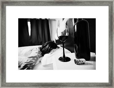 Half Full Glass Of Wine On Bedside Table Of Early Twenties Woman In Bed In A Bedroom Framed Print by Joe Fox