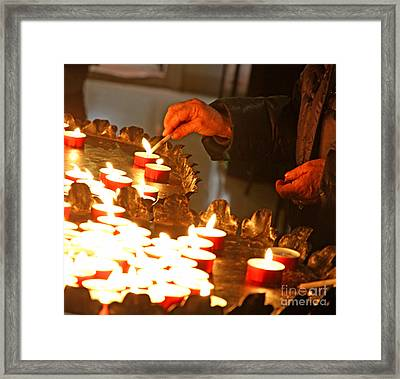 Hands Of An Elderly Woman Lighting A Candle Framed Print by Federico Candoni