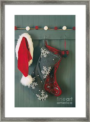 Framed Print featuring the photograph Hanging Stockings And Santa Hat On Hook by Sandra Cunningham