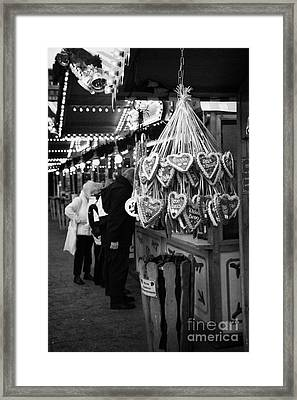 heart shaped Lebkuchen hanging on a christmas market stall with tourists browsing in Berlin Germany Framed Print
