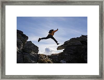 Hiker Leaps Between Rocks Near Noatak Framed Print