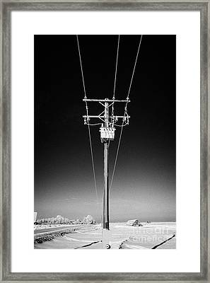 hoar frost covered overhead electricity transmission lines and pole transformer rural Canada Framed Print by Joe Fox
