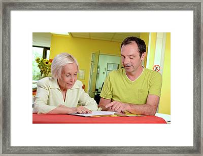 Hospital Nurse Assisting Elderly Woman Framed Print by Aj Photo