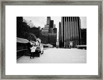 ice clearer and assistants clearing the ice at Bryant Park ice skating rink new york Framed Print by Joe Fox