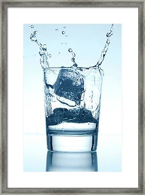 Ice Cube Falling Into A Glass Of Water Framed Print