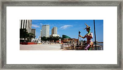 Jester Statue With Buildings Framed Print by Panoramic Images