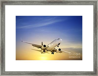Jet Aeroplane Landing At Sunset Blue Yellow  Framed Print by Colin and Linda McKie