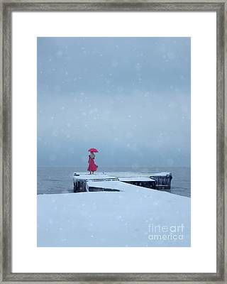 Lady In Red On Snowy Pier Framed Print
