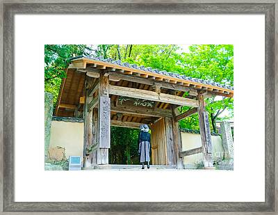Lady Looking Up At The Impressive Woodwork Of A Japanese Temple Gate Framed Print
