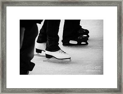 legs and feet of people ice skating on an outdoor rink for christmas Berlin Germany Framed Print by Joe Fox