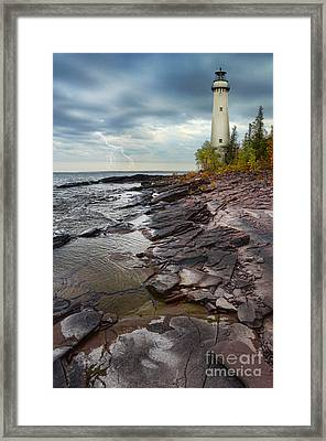 Lighthouse And Stormy Sea Framed Print