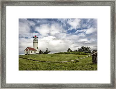 Lighthouse In The Clouds Framed Print by Jon Glaser