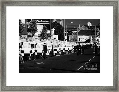 Line Of Psni Land Rovers And Officers On Crumlin Road At Ardoyne Shops Belfast 12th July Framed Print by Joe Fox