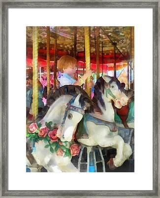 Little Boy On Carousel Framed Print by Susan Savad