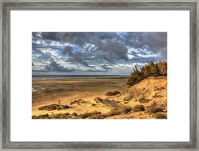 Lone Stroller On A Vast Beach Under Dramatic Sky Framed Print