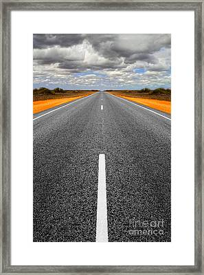 Long Straight Road With Gathering Storm Clouds Framed Print by Colin and Linda McKie