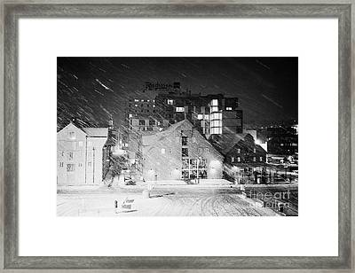 looking out atTromso bryggen quay harbour on a cold snowy winter night troms Norway europe Framed Print
