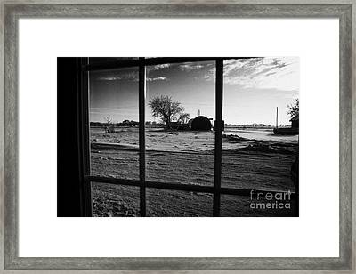 looking out through door window to snow covered scene in small rural village of Forget Saskatchewan  Framed Print