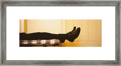 Low Section View Of A Man Lying On The Framed Print