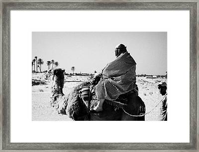 male tourist in desert clothing being led on the back of a camel into the sahara desert at Douz Tunisia Framed Print by Joe Fox