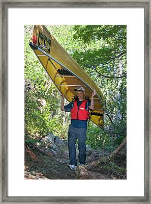 Man Carrying A Canoe Framed Print by Jim West