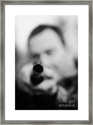 Man In Camouflage Clothes Takes Aim At Camera With Shotgun Close Up  On December Shooting Day Framed Print by Joe Fox