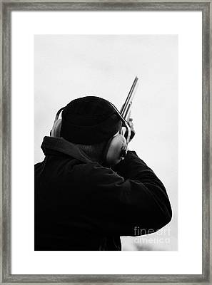 Man In Cap And Ear Defenders Takes Aim Into Sky With Shotgun On December Shooting Day Framed Print by Joe Fox