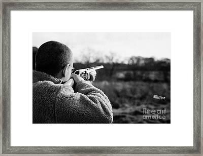 Man In Fleece Jacket Firing Shotgun Into Field With Cartridge Ejecting On December Shooting Day Framed Print by Joe Fox