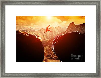 Man Jumping Over Precipice In Mountains Framed Print