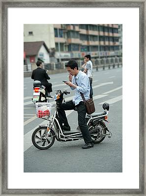 Man On A Battery-powered Moped Smoking Framed Print by Tony Camacho