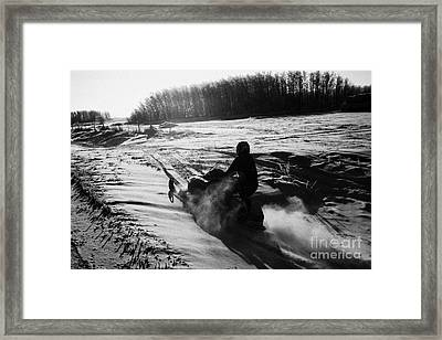 man on snowmobile crossing frozen fields in rural Forget canada Framed Print