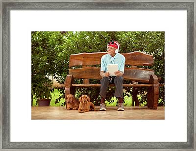 Man Sitting On Bench With Dogs Framed Print by Ktsdesign