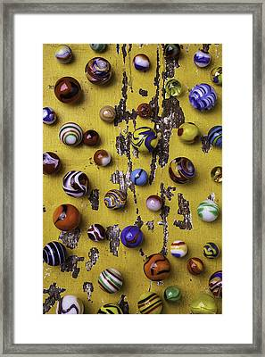 Marbles On Yellow Wooden Table Framed Print
