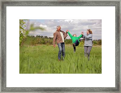 Mature Couple Swinging Grandchild In Framed Print by Bloom Productions