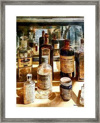 Medicine Bottles In Glass Case Framed Print by Susan Savad