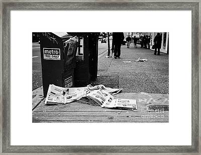 metro free newspapers thrown discarded on the sidewalk Vancouver BC Canada Framed Print
