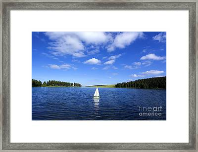 Miniature Sailboat In The Middle Of A Lake Framed Print by Bernard Jaubert