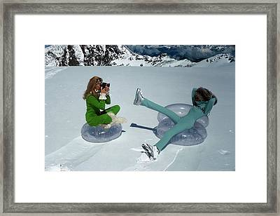 Models On Plastic Chairs With Snow In Switzerland Framed Print