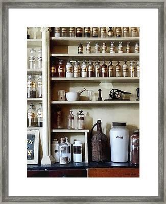 Mortar And Pestle And Bottles On Shelves Framed Print by Susan Savad