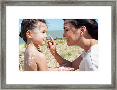 Mother Applying Suncream To Daughter Framed Print by Ian Hooton
